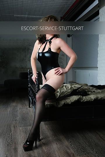 Escort Böblingen Daniela posiert in einem sexy schwarzen Outfot mit schwarzen High Heels an der Ecke eines Bettes