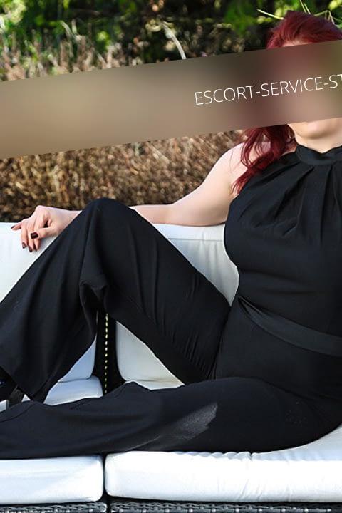 Escort Jule posiert auf Möbeln im Freien in einem schwarzen Outfit und schwarzen Schuhen.