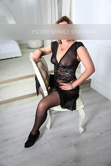 Escort Paulina posiert rückwärts in einem Stuhl mit schwarzem Negligé und schwarzen Schuhen mit hohen Absätzen