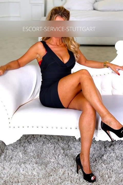 Linda posiert auf einer Couch in einem schwarzen Kleid und schwarzen High Heels