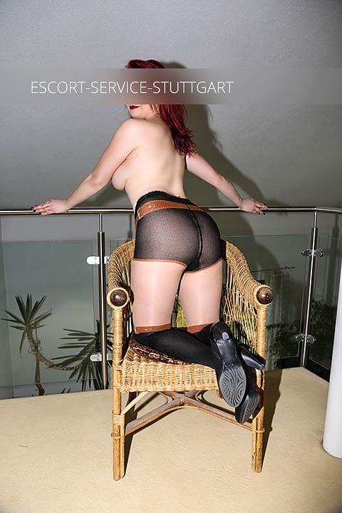 Escort Jule posiert auf einem Stuhl und trägt oben ohne Schuhe