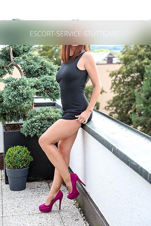 Escort Vivien posiert in einem sexy schwarzen Kleid mit violetten Schuhen mit hohen Absätzen von der Seite