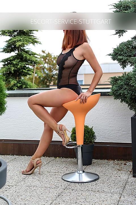 Escort Vivien posiert draußen auf einem Barhocker in einem sexy schwarzen Dessous-Outfit