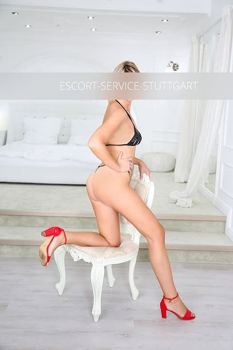 Escort Sandra posiert mit einem Knie auf einem Stuhl in schwarzen Dessous und roten Schuhen mit hohen Absätzen