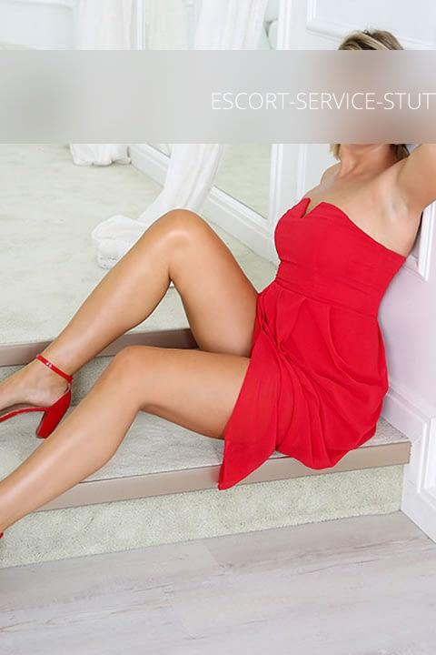 Escort Sandra posiert in einem roten Kleid und roten High Heels auf einer Stufe