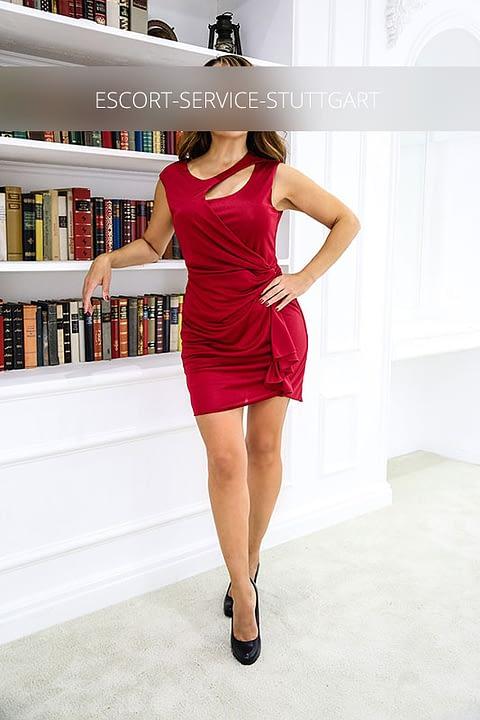 Michelle posiert stehend mit einer Hand an der Hüfte in einem sexy roten Kleid und schwarzen Schuhen
