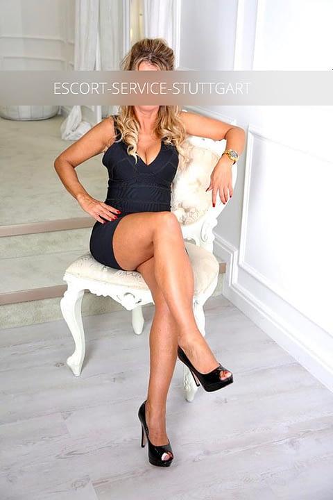 Escort Linda posiert auf einem Stuhl mit gekreuzten Beinen in einem schwarzen Kleid und Schuhen