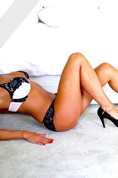 Linda posiert auf dem Boden auf dem Rücken in sexy Dessous und Schuhen mit hohen Absätzen
