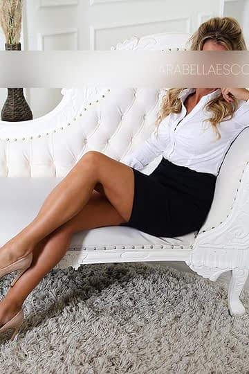 Escort Linda wearing a white blouse and black skirt setting on a sofa